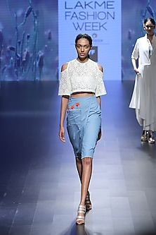 Off white cold shoulder croptop and denim poppy wrap skirt by Nishka Lulla
