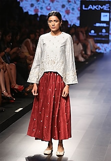 Powder blue embroidered high low tunic and pomegranate skirt set by Payal Singhal