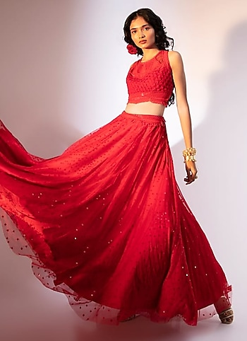 Channel your blushing glow in this red embroidere lehenga ensemble by Ekta Singh. Complete the look with blingy statement pieces by Colour Me Red