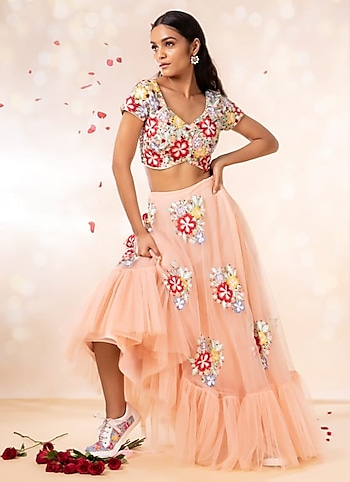 Turn heads as you enter the wedding soirée in a floral embellished tulle lehenga. Complete your preppy look with dainty baubles and statement-making sneakers. by Flower Power