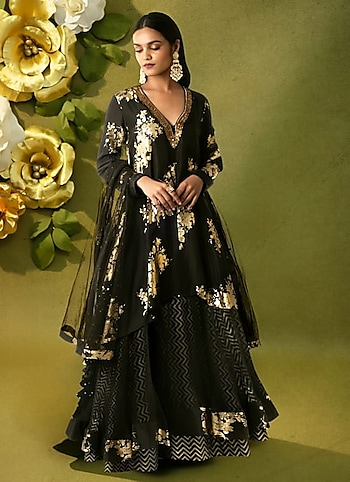 Revive the age of gradeur in an opulent black kurta styled lehenga for Eid. Complete your royal look with a pair of statement danglers and a ring. by Festive Granduer