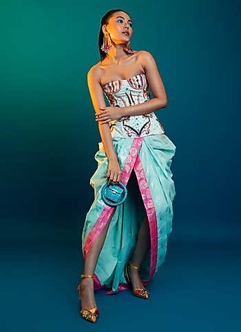 Seeking a glamour quotient that stands out? Experiment with unconventional draping with a bright Masaba saree pairing it with an artsy corset by Manish Arora. A miniaudiere bag and statement earrings are all you need to anchor the glam by Extra Dose of Glam