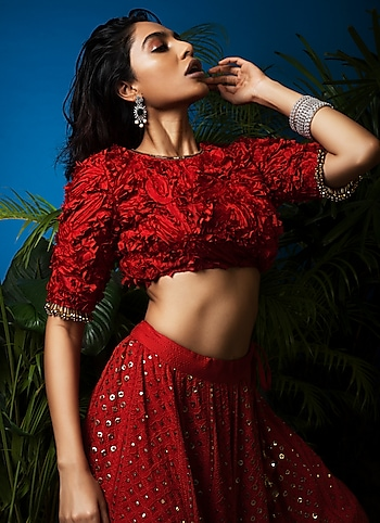 A contemporary festive look with a 3-D ornated lehenga ensemble paired with a dainty pair of earrings and stacked bracelets for a whimsical appeal. by FESTIVE TREASURE