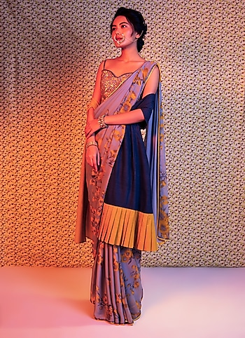 Drape yourself in the allure of this exquisite saree by Adah styling it with a stole. Punctuate the look with nose ring and statement bracelets to perfect the fusion flair by Sassy In Saree
