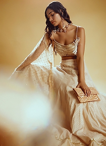 Channel your exquisite flair at the destination wedding in this cream embellished lehenga by Izzumi Mehta. Accentuate your look with contemporary jewels by Outhouse. by Whimsical Allure