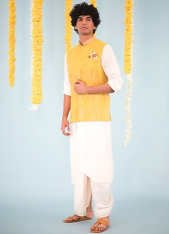 Enliven the festive spirit in this set of white kurta and dhoti pants by Bohame pairing them with a bright mustard bundi jacket. by Bright Basics