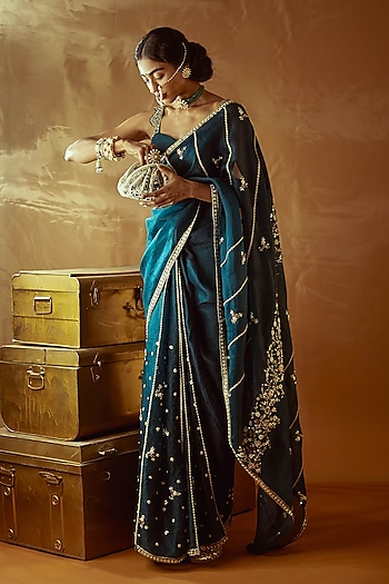 Channel your grace in this emerald green saree by Nadima Saqib. Accentuate the look with traditional pieces from Riana Jewellery and a vintage pouch by Lovetobag by Quintessential Indian