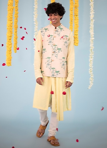 Keep it understated in this draped kurta from Unit by Rajat Suri pairing it with a floral printed bundi jacket by Project Bandi by Well-Heeled Groomsman