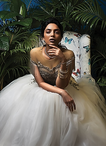 A stunning soirée look with an opulent embellishment accented white gown paired with stacked bangles and a dainty pair of earrings and necklace. by BELLE OF THE BALL