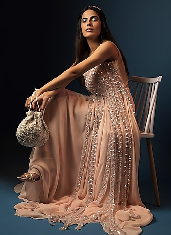 Imbibe a dash of drama into your evening look in this peach gown by Diya Rajvvir adorning floor-grazing tassels. by SHIMMER-CLAD